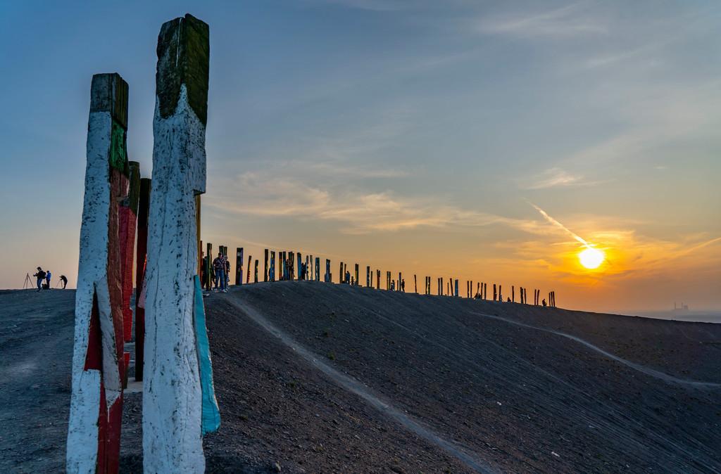 JT-200407-067   Die Halde Haniel, 185 Meter hohe Bergehalde, am 2019 stillgelegtem Bergwerk Prosper Haniel, Kunstwerk Totems des Bildhauers Augustin Ibarrola, Sonnenuntergang, Bottrop, Deutschland,