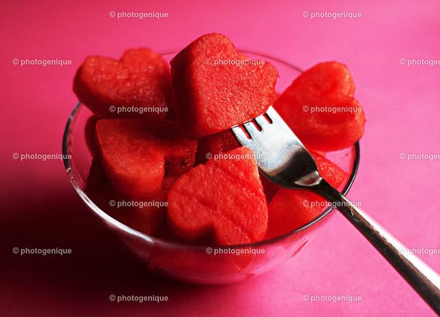 Melonenherzen | eine Schüssel voll Melone in Herz-Form mit Gabel angespießt vor einem roten Hintergrund bei Tageslicht