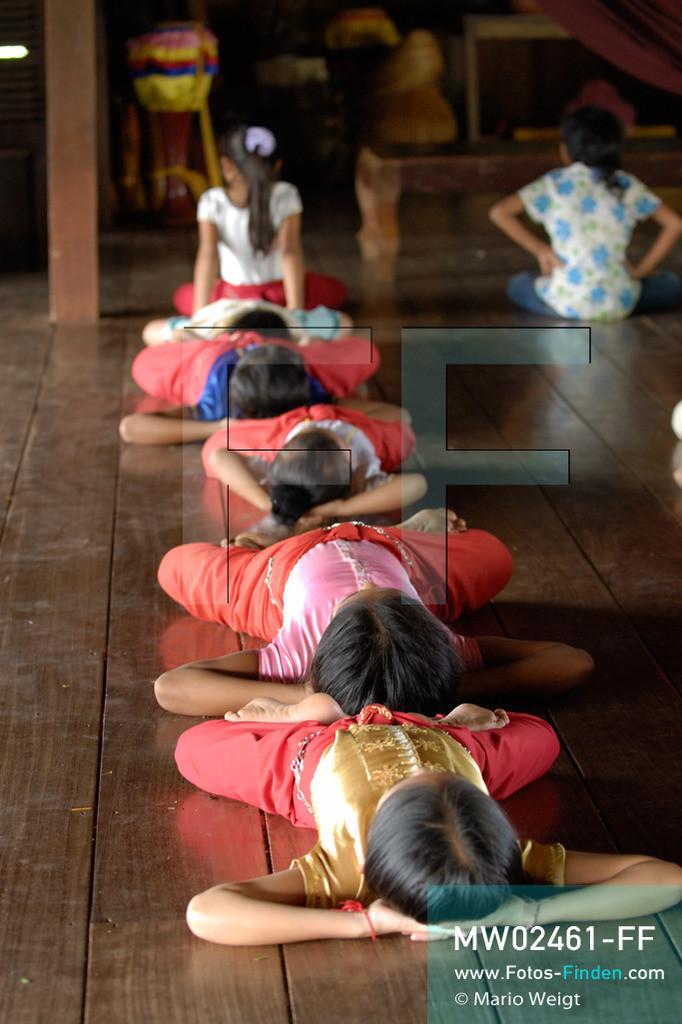 MW02461-FF | Kambodscha | Phnom Penh | Reportage: Apsara-Tanz | Für die Schülerinnen der Tanzschule beginnt jede Tanzstunde mit Aufwärmübungen. Sechs Jahre dauert es mindestens, bis der klassische Apsara-Tanz perfekt beherrscht wird. Kambodschas wichtigstes Kulturgut ist der Apsara-Tanz. Im 12. Jahrhundert gerieten schon die Gottkönige beim Tanz der Himmelsnymphen ins Schwärmen. In zahlreichen Steinreliefs wurden die Apsara-Tänzerinnen in der Tempelanlage Angkor Wat verewigt.   ** Feindaten bitte anfragen bei Mario Weigt Photography, info@asia-stories.com **