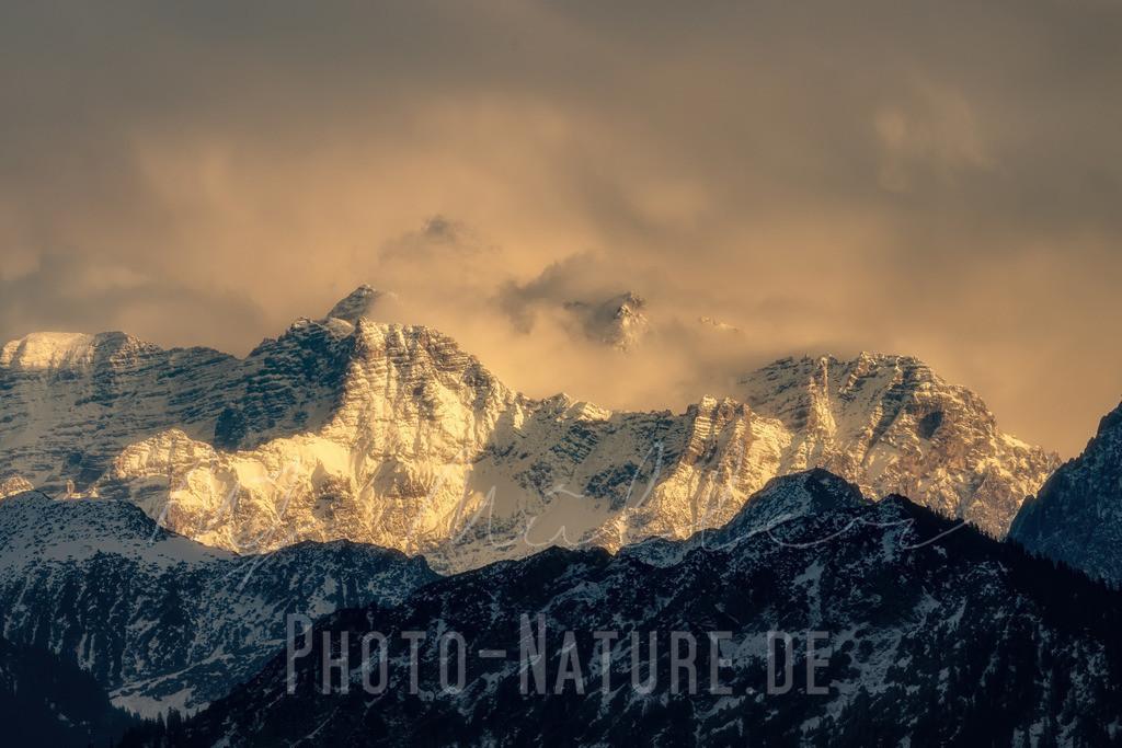 Gewaltiges Bergmassiv in den Wolken | Dieses Bergmassiv erhob sich durch die dichten Wolken und glänzte in den letzten Sonnenstrahlen.