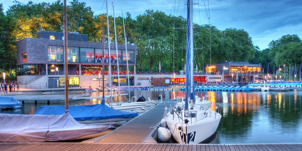 Neuer Bootshafen am Aasee in Münster | Neuer Aasee-Bootshafen an den Aasseeterassen mit Segelbooten und Gastronomie in der blauen Stunde