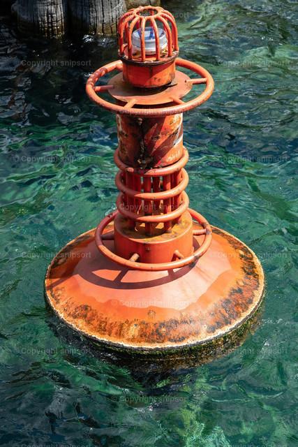 Orangene Buje | Eine orangenfarbene Buje im grünlich schimmernden klaren Wasser im Hafen.