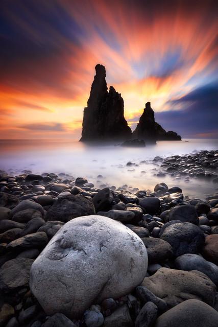 The Rock | Es gibt nicht viele perfekte Momente im Leben eines Fotografen. Dieser hier war einer. Die spektakuläre Küste an der Nordseite Madeiras ist Grund genug, den Auslöser klicken zu lassen. Die Farben an diesem Morgen zum Sonnenaufgang waren allerdings überirdisch. Als der heftige Wellengang weitere Motive nahe am Wasser unmöglich machten, gaben die großen Steine am Strand den idealen Vordergrund ab.