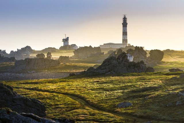 Sonnenaufgang auf Ouessant | Bis auf die ausgefranste Küste ist die kleine Insel Ouessant mit einem grünen Teppich aus Gras bedeckt. Hier am Leuchtturm Phare du Créac'h modelliert das erste Licht des Tages mit seinen langen Schatten die karge Landschaft.