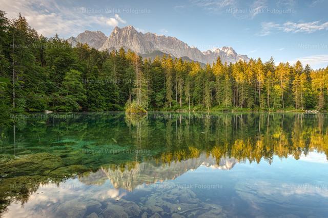 Badersee in Bayern   Der Badersee liegt in Grainau bei Garmisch-Partenkirchen in Bayern. Es ist ein kleiner Bergsee mitten in einem Wald mit Blick auf die dahinterliegenden Berge. Der hohe Gipfel links neben der Bildmitte ist der Große Waxenstein, rechts im Hintergrund ist die Zugspitze zu sehen.