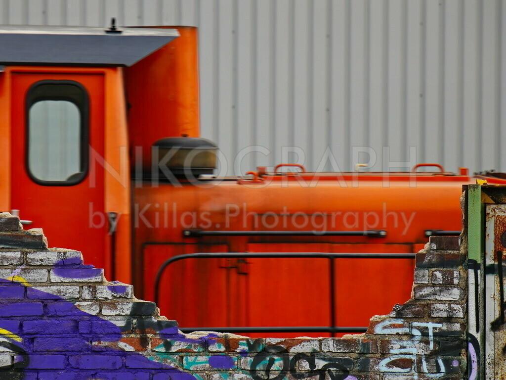 Werkbahn hinter Mauerrest   Die Lokomotive einer Werkbahn hinter Mauerresten, die mit Graffiti besprüht sind.