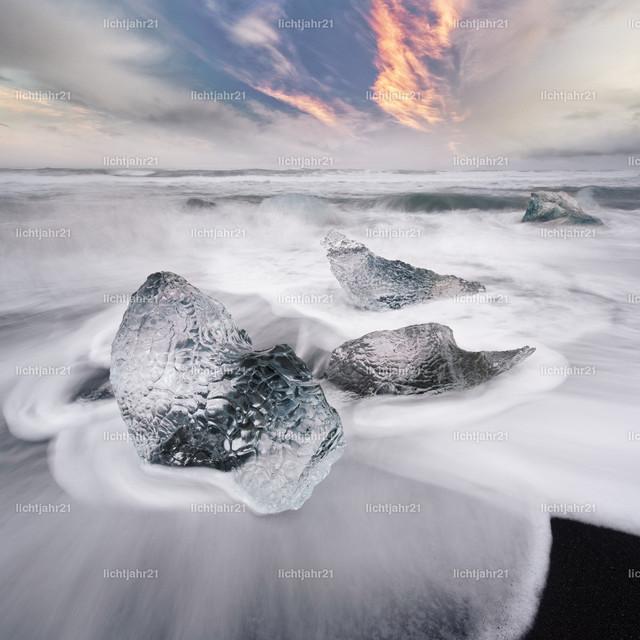 Eisblock und Wellen | Eisblöcke an einem Strand mit starker Brandung, die Dynamik einer Welle ist zu sehen (Langzeitbelichtung, Bewegungsspuren), darüber markante vom Abendlicht rötlich gefärbte Wolken - Location: Island, Jökulsarlon (Jökulsárlón)