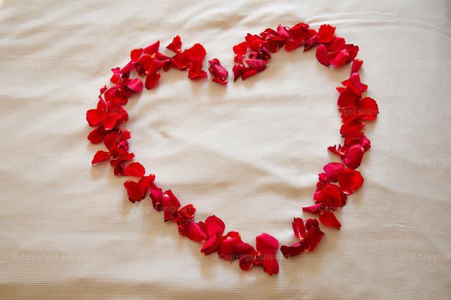 Herz aus Rosen auf einem Bettlaken | Herz aus Rosen auf einem Bettlaken in einem Hotel