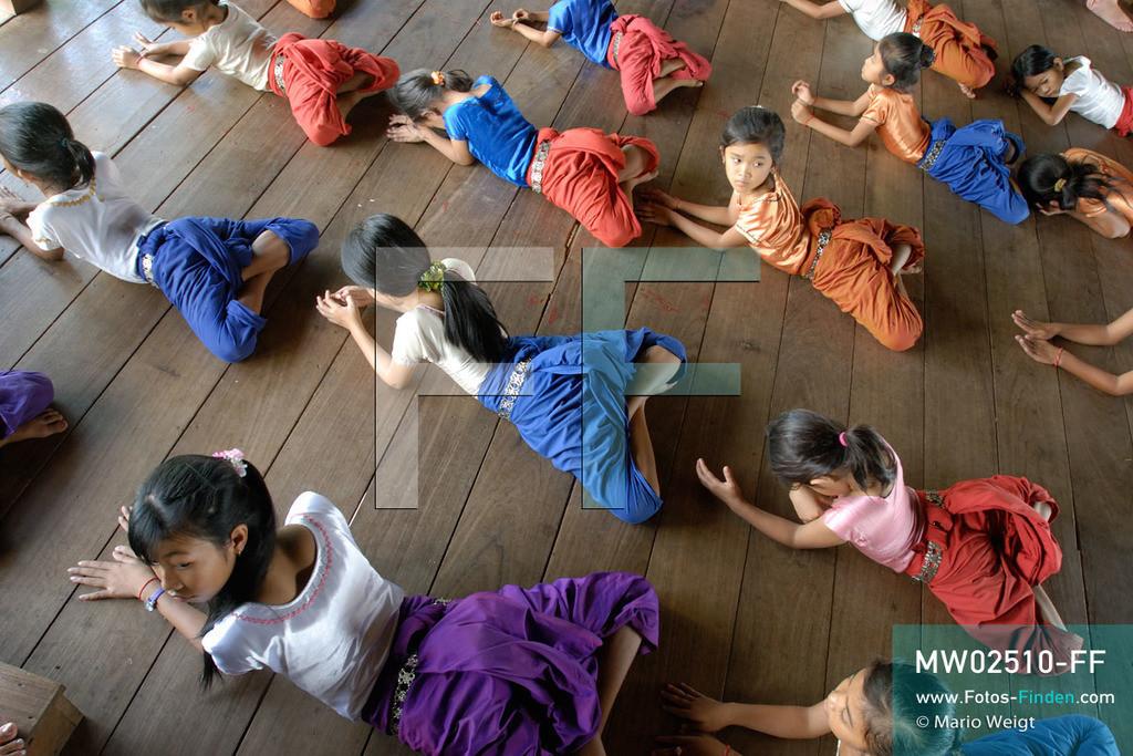 MW02510-FF | Kambodscha | Phnom Penh | Reportage: Apsara-Tanz | Schülerinnen beginnen die Tanzstunde mit Dehnübungen. Sie lernen den Apsara-Tanz in einer Tanzschule. Sechs Jahre dauert es mindestens, bis der klassische Apsara-Tanz perfekt beherrscht wird. Kambodschas wichtigstes Kulturgut ist der Apsara-Tanz. Im 12. Jahrhundert gerieten schon die Gottkönige beim Tanz der Himmelsnymphen ins Schwärmen. In zahlreichen Steinreliefs wurden die Apsara-Tänzerinnen in der Tempelanlage Angkor Wat verewigt.   ** Feindaten bitte anfragen bei Mario Weigt Photography, info@asia-stories.com **