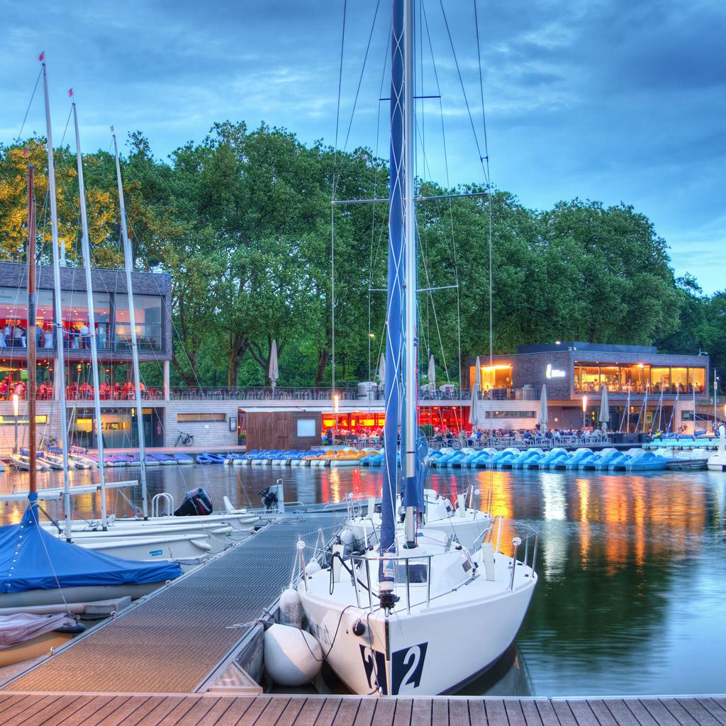 Neuer Bootshafen am Aasee in Münster   Neuer Aasee-Bootshafen an den Aasseeterassen mit Segelbooten und Gastronomie in der blauen Stunde