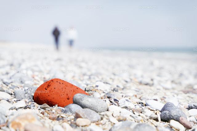 Steinstrand auf Helgoland | Heller Steinstrand mit einem auffallenden roten Stein im Schärfebereich, dahinter schemenhaft 2 Personen und das Meer - Naheinstellung, Perspektive - Location: Deutschland, Nordsee-Insel Helgoland