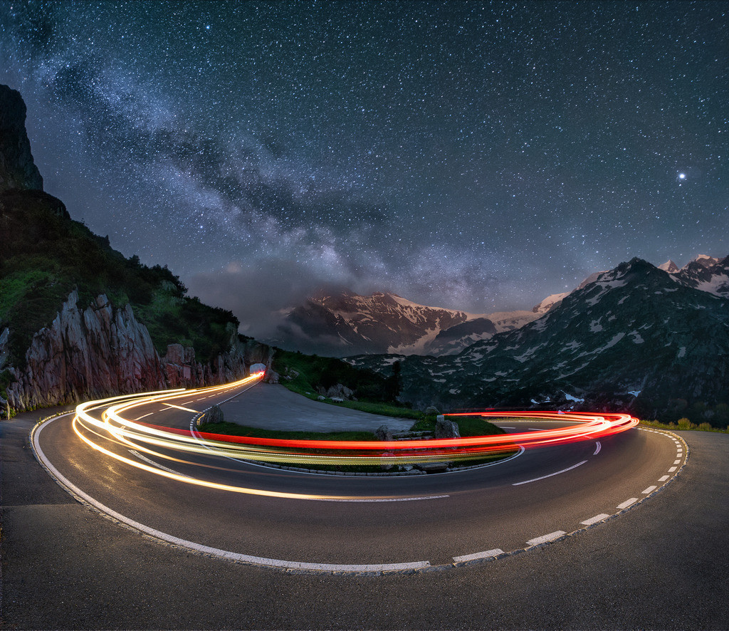 Bending Time | Milky way and light trails on a swiss alpine road.