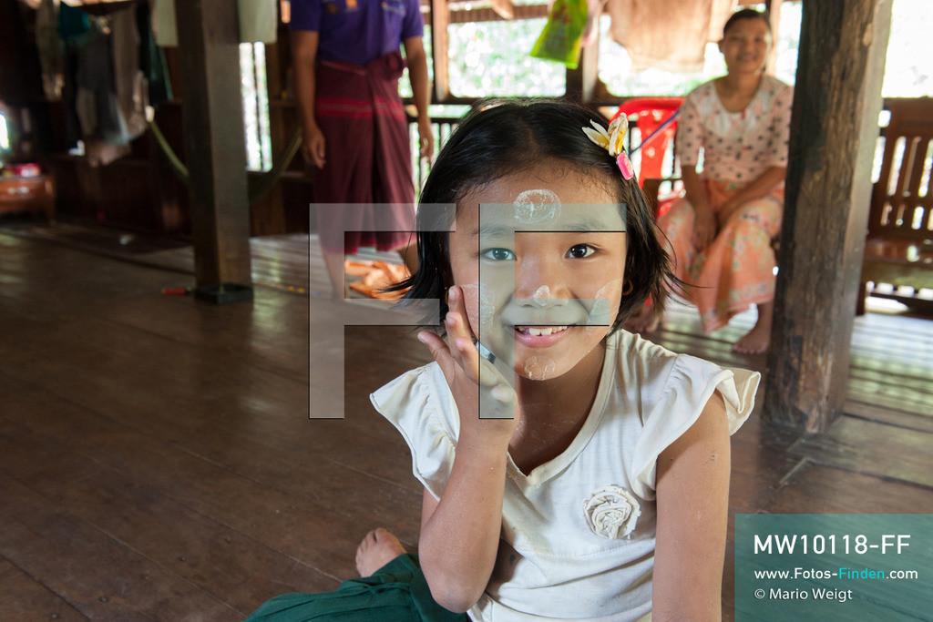 MW10118-FF | Myanmar | Hpa-an | Reportage: Zin mag Thanaka-Paste | Zin mit Thanaka-Paste im Gesicht im Wohnhaus. Die 7-jährige Nwe Zin Aye lebt im Dorf La Ka Nha nahe der Stadt Hpa-an. Sie bemalt gern ihr Gesicht mit Thanaka-Paste. Nach der burmesischen Tradtition tragen fast alle Mädchen und Frauen diese Art von Schminke.   ** Feindaten bitte anfragen bei Mario Weigt Photography, info@asia-stories.com **
