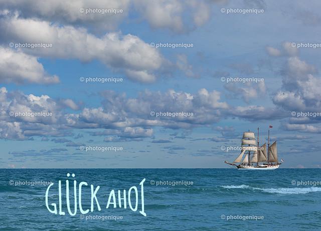 Postkarte Urlaubskarte Grußkarte Glück ahoi | Postkarte Urlaubskarte Grußkarte mit einem weißen Segel-Schiff auf dem Meer vor blauem Himmel mit Wolken bei Tageslicht und dem Spruch Glück ahoi