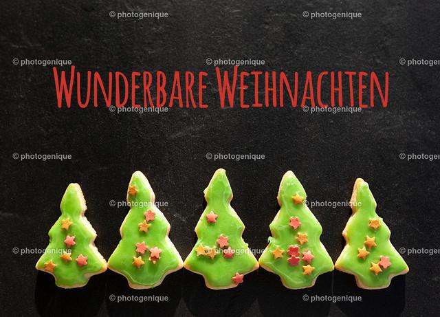 Weihnachtskarte fünf Weihnachtsbäume wünschen wunderbare Weihnachten | Weihnachtskarte mit fünf Weihnachtsbaum-Plätzchen wünschen wunderbare Weihnachten vor einem dunklen Hintergrund bei Tageslicht
