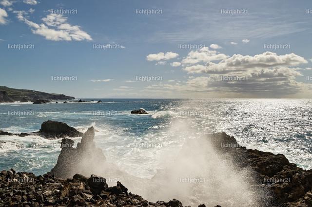 Gischttropfen einer Welle am Steinstrand | Starke Brandung an einem schwarzen Vulkanstrand mit Steinen, Gischttropfen einer Welle im Gegenlicht, Sonnenreflektion auf dem Wasser - Location: Spanien, Kanarische Inseln, La Palma