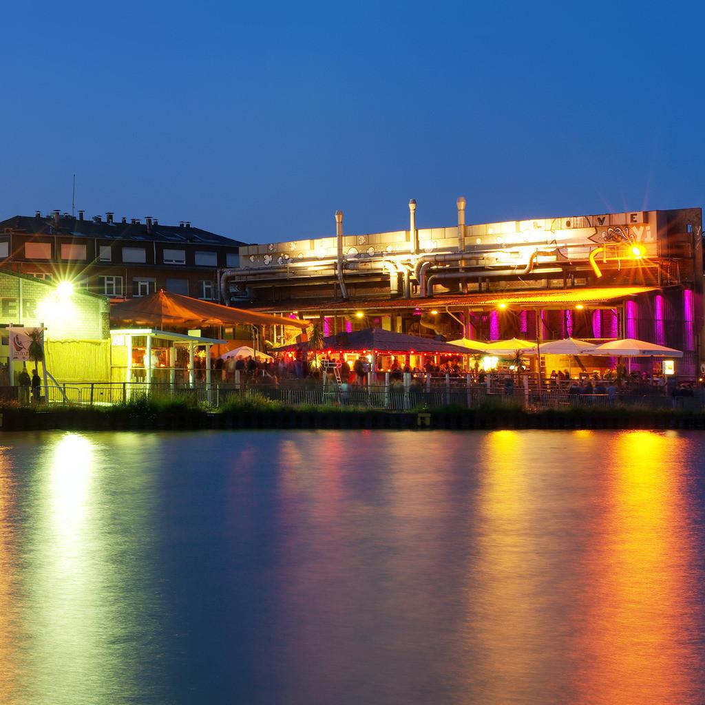 """Münster Alter Hafen mit Strandbar bei Nacht   Alter Hafen Münster mit Strandbar   Motiv: Münster - Alter Hafen mit Strandbar bei Nacht (Art. 2004-PK) In den 1980er Jahren wurde der Hafen als günstiger Gewerberaum durch alternative Unternehmen, darunter linksgerichtete Verlage und Druckereien entdeckt. In den 1990er Jahren eröffnete die House-Discothek Dockland im Hafen. Mit Auslaufen der Erbpachtverträge für viele der Immobilien wurde das nördliche Ufer des Hafens als Kreativkai angelegt. In den Sommermonaten bis 2017 öffnete hier hier das """"Heaven"""" und die die Strandbar """"Coconut Beach"""" ihre Pforten."""