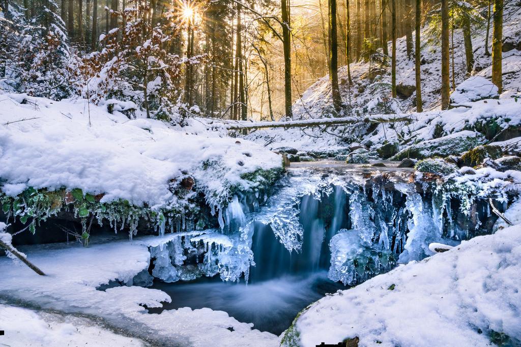 Winterlicher Gebirgsbach im Schwarzwald mit Eiszapfen, Schnee und Frost
