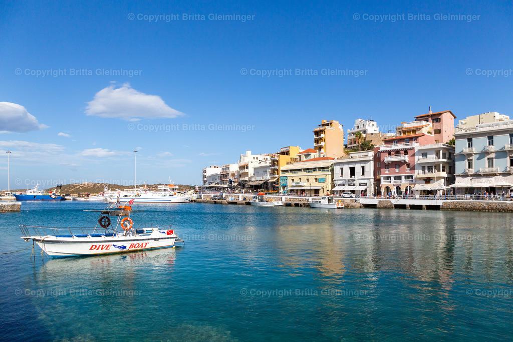 Port of Agios Nikolaos   Der Hafen von Agios Nikolaos, einer wunderschönen Stadt im nord-osten der Insel Kreta in Griechenland, hat glasklares, türkises Wasser. Fischerboote, Tauchboote und Ausflugsschiffe tummeln sich im Hafenbecken. Die Hafenpromenade ist gesäumt von bunten Häusern mit Cafés, Boutiquen und Restaurants. Mediterranes Flair kommt hier wirklich nicht zu kurz.