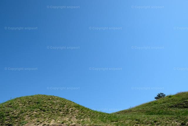 Zwei grüne Hügel | Zwei grasbewachsene grüne Hügel mit klarem blauem Himmel im Hintergrund.