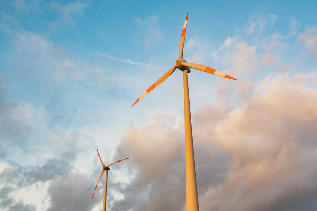 Mensch, Klima! | ecological renewable green energy wind power station on a field in evening sun