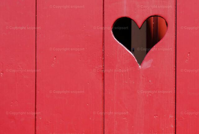 Toilettentür mit Herzausschnitt (Detail) | Rote Holzbretter von einem Toilettenhäuschen mit einem Herzchen.