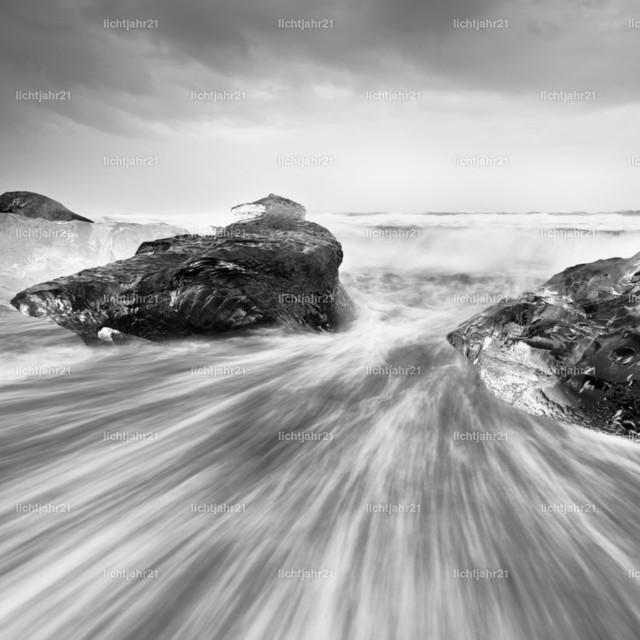 Eisblöcke in der Brandung | Schwarzweißbild von großen Eisblöcken an einem schwarzen Strand mit starker Brandung, die Wasserbewegung ist zu sehen (Langzeitbelichtung, deutliche Bewegungsspuren), darüber ein kontrastreicher grau bewölkter Himmel, Tiefenwirkung durch Perspektive - Location: Island, Jökulsarlon (Jökulsárlón)