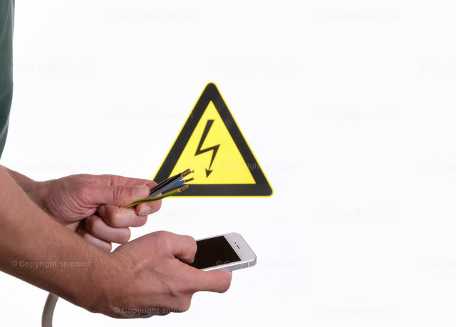 Mann prüft die Farben der Strippen am Handy | Konzept von einem Mann, der die Farben für die Stromadern am Smartphone nachschlägt.