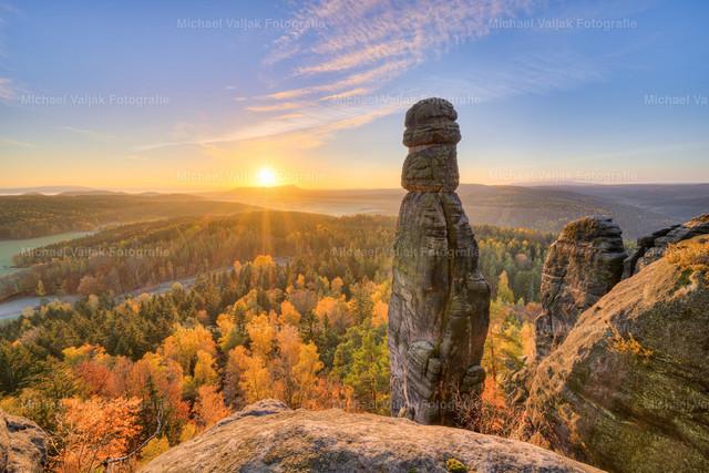 Barbarine bei Sonnenaufgang | Die 42,7 m hohe Barbarine beim Pfaffenstein ist einer der bekanntesten freistehenden Felsen der Sächsischen Schweiz und gleichzeitig ein Wahrzeichen der Region sowie ein Naturdenkmal. Die Aufnahme zeigt den imposanten Felsen kurz nach Sonnenaufgang im Herbst.