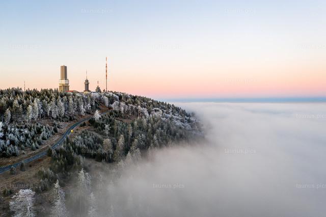 Sonnenuntergang bei Hochnebel und Raureif | 23.01.2020, Schmitten (Hessen): Winterlich zeigt sich der Gipfel des Großen Feldbergs im Taunus mit einer dicken Raureifschicht am späten Nachmittag kurz vor Sonnenuntergang. (Luftaufnahme mit einer Drohne)