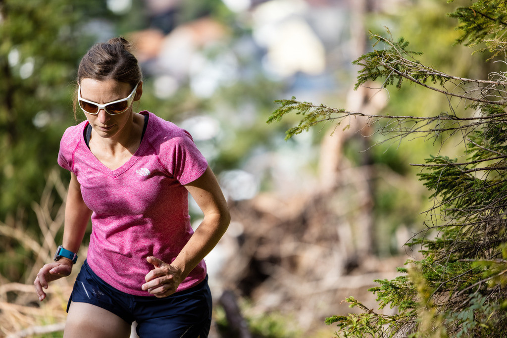 Young woman on a trail run (2) | A your woman is running uphills in the forest.