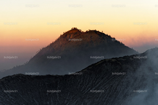 Erstes Tageslicht am aktiven Vulkan Ijen | Erstes Tageslicht am aktiven Vulkan Ijen, Blick vom ca. 3.000 Meter hoch gelegenen Kraterrand auf einen gegenüber liegenden Vulkankrater, der Himmel in den Farbtönen rosa bis gelb  - Location: Indonesien, Insel Java