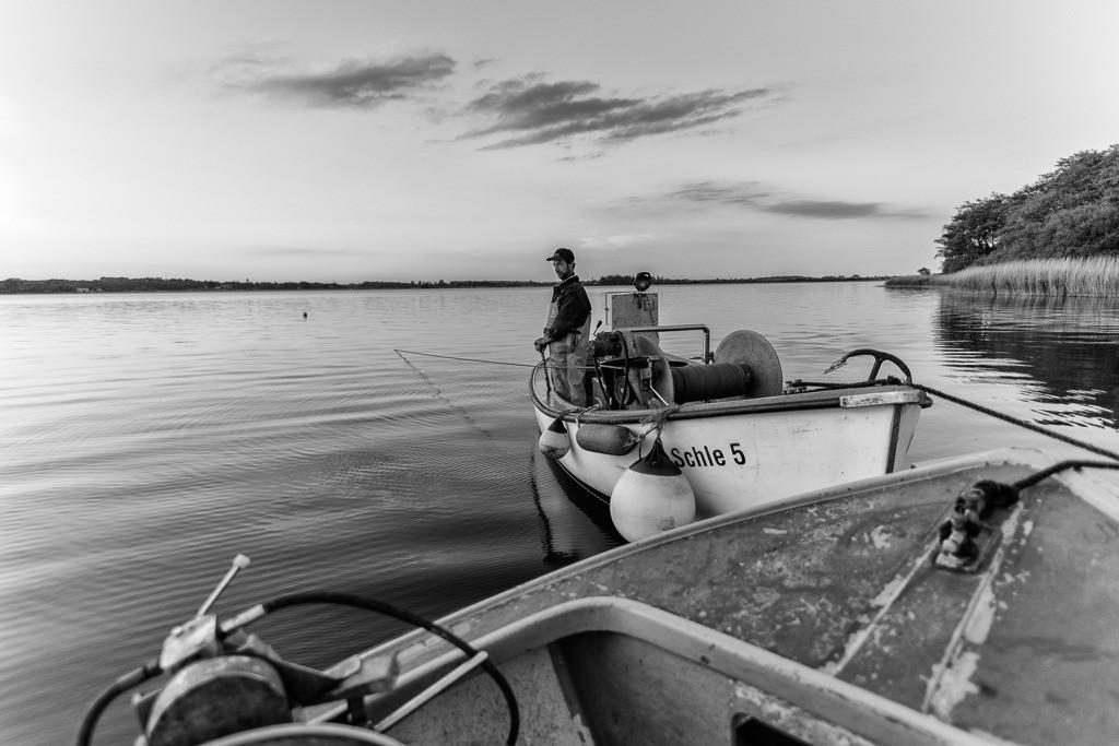 Wadenfischen auf der Schlei © Holger Rüdel | Fischer Nils Ross aus Schleswig wartet auf das Zeichen zum Einholen der Wade. Dieses große Zugnetz wird hier von zwei Booten gleichzeitig ausgebracht und wieder eingeholt.