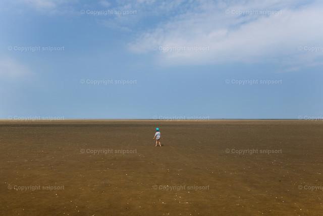 Kleiner Junge im trockenen Wattenmeer | Ein kleiner Junge allein im Watt als Konzept für große, weite Welt.
