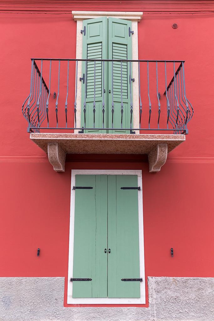Fenster mit Balkon in Grün und Rot
