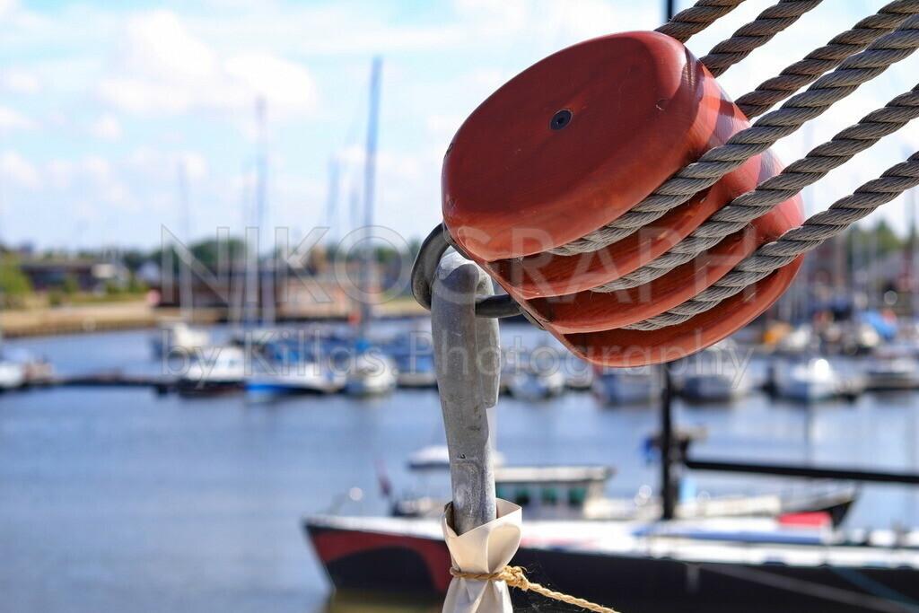Talje und Läufer | Ein Flaschenzug vor der Hafenkulisse im Hintergrund. In der Seefahrt wird der Flaschenzug auch Talje genannt.