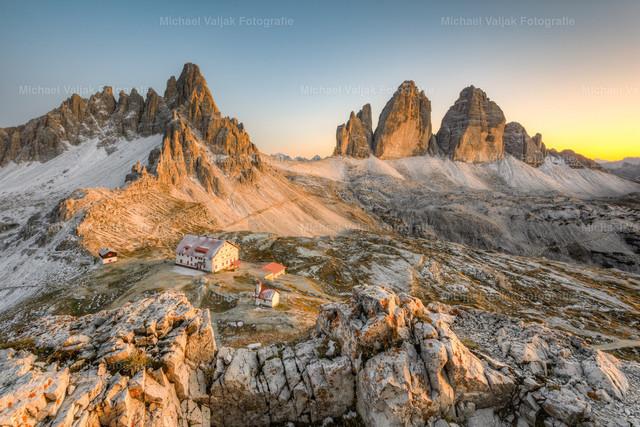 Drei Zinnen in der Abenddämmerung | Blick über die Dreizinnenhütte zum Paternkofel und zu den Drei Zinnen. Noch lange nach Sonnenuntergang taucht die Abenddämmerung die Landschaft in ein warmes Licht.