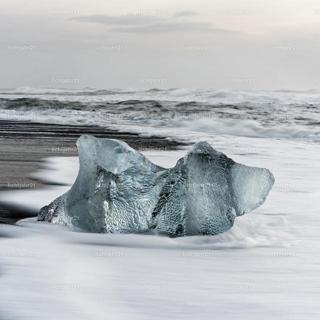 Eisblock am schwarzen Strand | Markanter Eisblock in blauen Farbtönen an einem schwarzen Strand mit starker Brandung, Gischt auf dem dunklen Sand, im Hintergrund rollen Wellen heran - Location: Island, Jökulsarlon (Jökulsárlón)