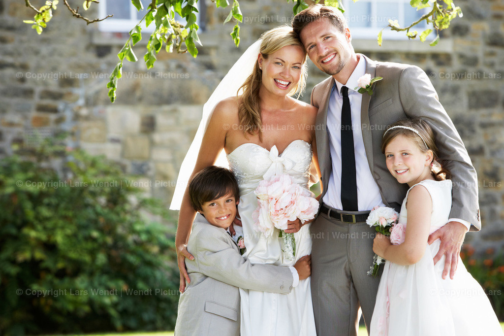 184753930 | Bride And Groom With Bridesmaid And Page Boy At Wedding Smiling To Camera