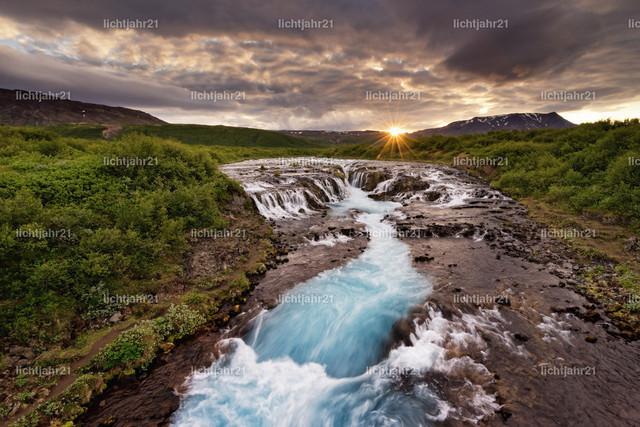 Wasserfall in wilder Landschaft mit Sonnenuntergang | Großer Wasserfall in einer weiten Landschaft bei Abendlicht, Sonnenuntergang mit Strahlen an einer Bergkette, Wasserbewegung in Langzeitbelichtung - Location: Island, Golden circle, Bruarfoss