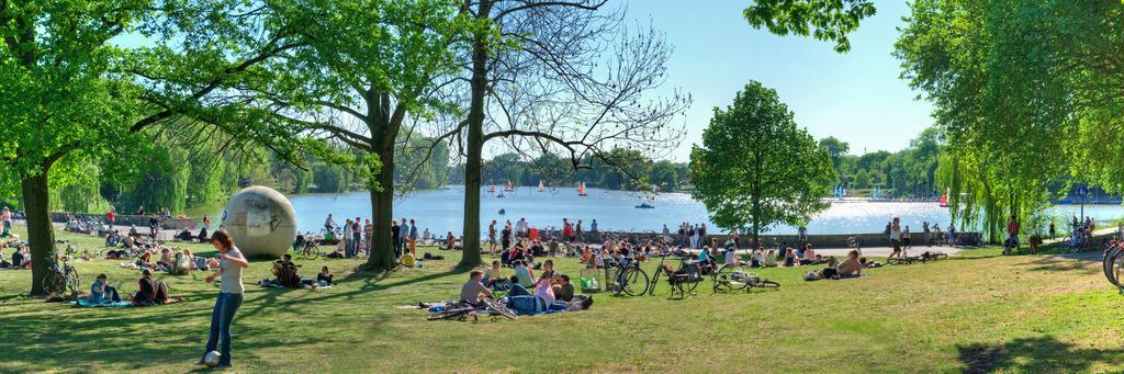 Münsteraner Aasee-Wiesen im Sommer   Junge Leute machen Picknik im Sommer am Aasee auf den Aasee-Wiesen in Münster mit viel grüner Wiese, Bäumen und Segelboote auf dem Wasser
