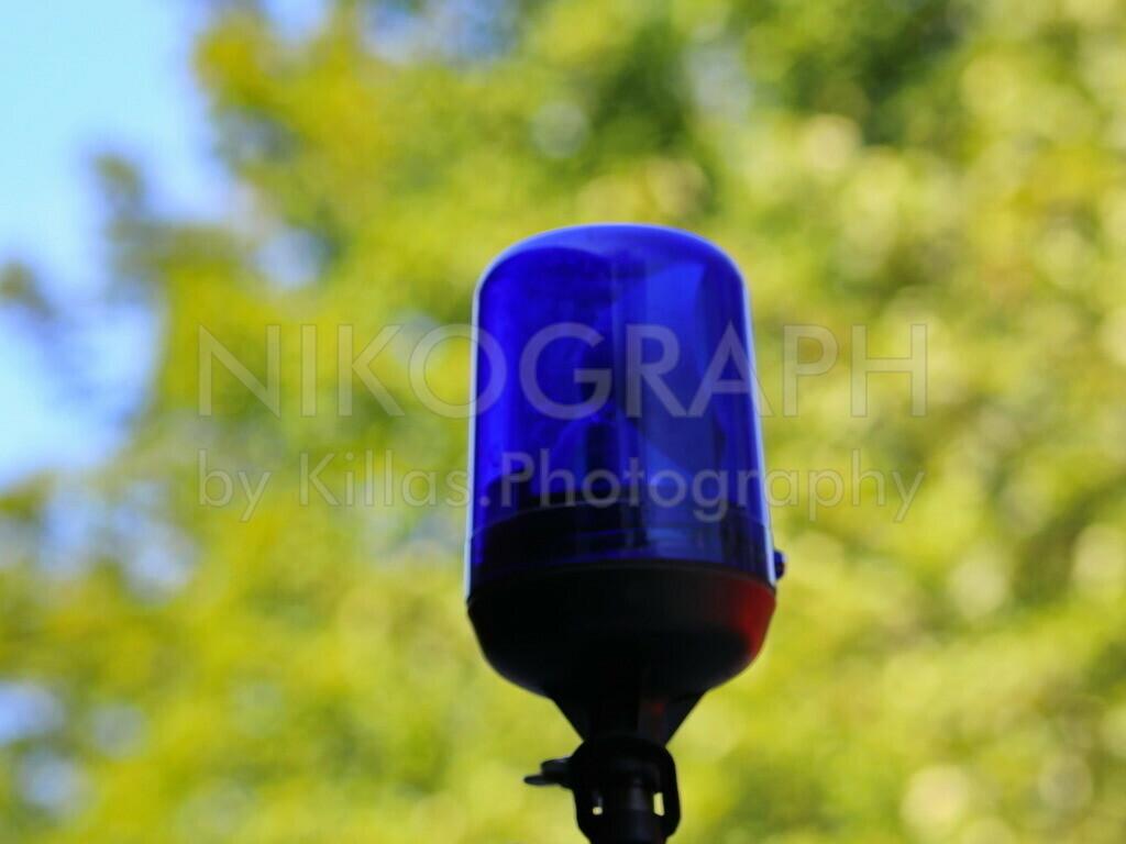Rundumkennleuchte   Ein Blaulicht vor dem Blätterwald.
