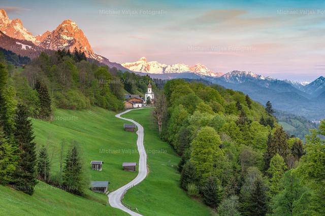 Frühlingsmorgen in Wamberg   Ein wunderschöner und friedlicher Frühlingsmorgen im Kirchdorf Wamberg bei Garmisch-Partenkirchen in Bayern, langsam erwacht der Tag und die ersten Sonnenstrahlen tauchen die Berge in ein rotes Licht.
