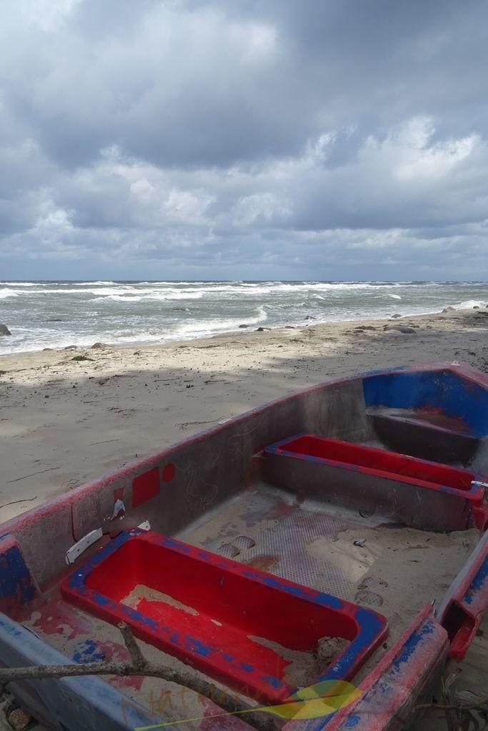 Buntes Strandgut | Wundervolle Farben: das bezaubernde Boot und der Ostseestrand mit dem wolkenverhangenen Himmel. Eintauchen und träumen!