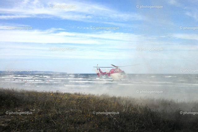 Hubschrauber landet in Prora am Strand   Hubschrauber landet am Strand bei Tageslicht vor einem hellen Hintergrund und wirbelt Dreck auf