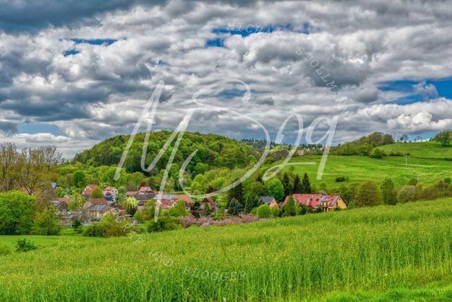 Hetschburg  | Hetschburg im Frühling, Grüne Landschaft mit einem malerischem Dorf vor imposanter Wolkenkulisse