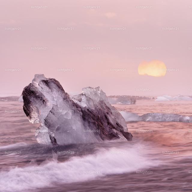 Sonnenuntergang mit Eisblöcken | Eisblöcke an einem Strand mit starker Brandung, die Wasserbewegung ist zu sehen (Langzeitbelichtung, Bewegungsspuren), die große untergehende Sonne bringt rötliche Farbtöne in das Bild, Tiefenwirkung durch Perspektive - Location: Island, Jökulsarlon