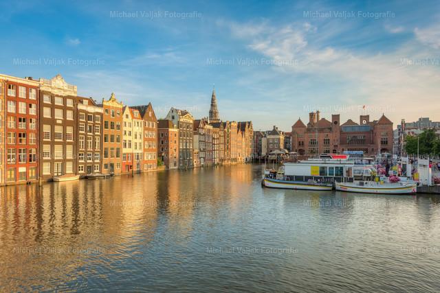 Amsterdam Damrak in der Abendsonne   Blick auf die Häuser am Damrak-Kanal in Amsterdam im warmen Licht der Abendsonne.