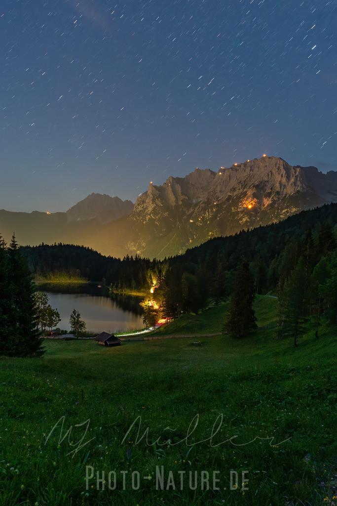 Die Berge in Flammen   Ein idyllischer Bergsee im Karwendel mit den Johannifeuer im Hintergrund