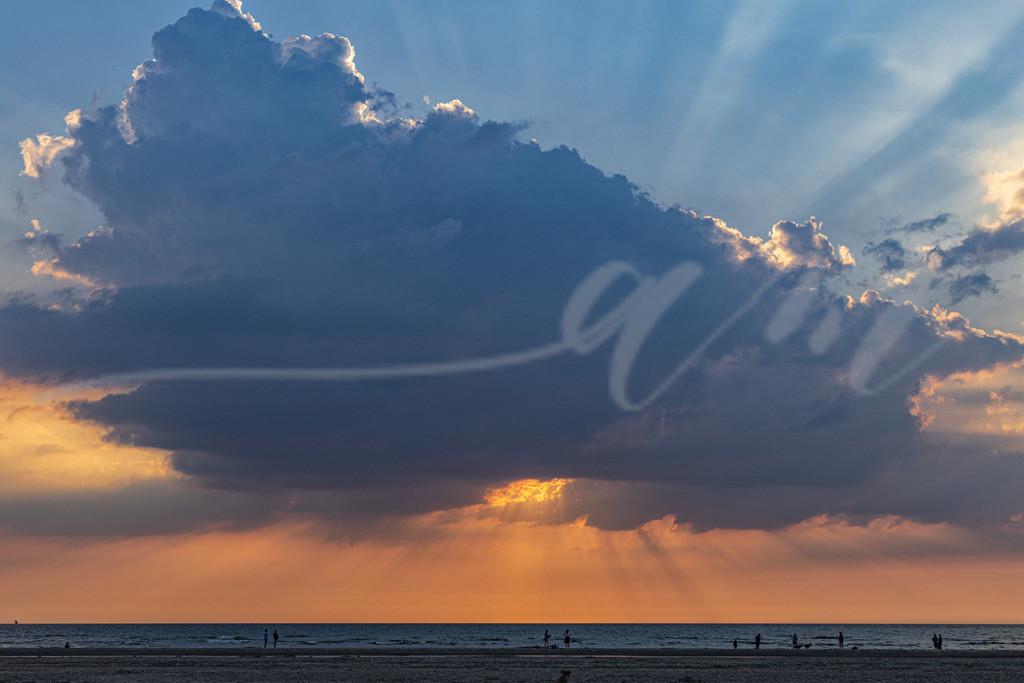 Momente... | Sonnenstrahlen hinter einer großen Wolke über der Nordsee, fotografiert vom Strand in Sankt Peter-Ording